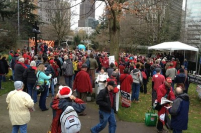 Roughly 300 activists, many dressed in red, gathered in a park outside the Washington Convention Center to protest a proposal to build a coal port terminal north of Bellingham. (Brian M. Rosenthal / The Seattle Times)