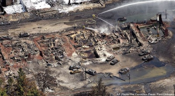 The downtown core lays in ruins as fire fighters continue to water smoldering rubble Sunday, July 7, 2013 in Lac Megantic, Quebec after a train derailed ignited tanker cars carrying crude oil.