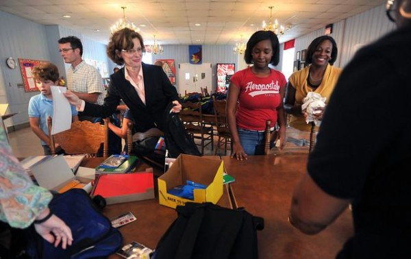 File - With the help of son, Vinson, left, and husband Ron, U. S. Senate candidate Michelle Nunn Martin and other volunteers stuff book bags with school supplies for residents of the Georgia Industrial Children's Home on Aug. 7, 2013.    Beau Cabell/The Telegraph/AP Images