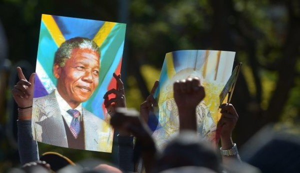 People hold a portrait of Nelson Mandela as they stand in line to pay respect to late South African president Nelson Mandela in Pretoria, South Africa, December 12, 2013. | Photo by AFP