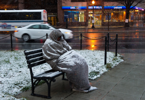 A homeless man sits covered in snow early in Washington, DC. | AFP Photo / Karen Bleier