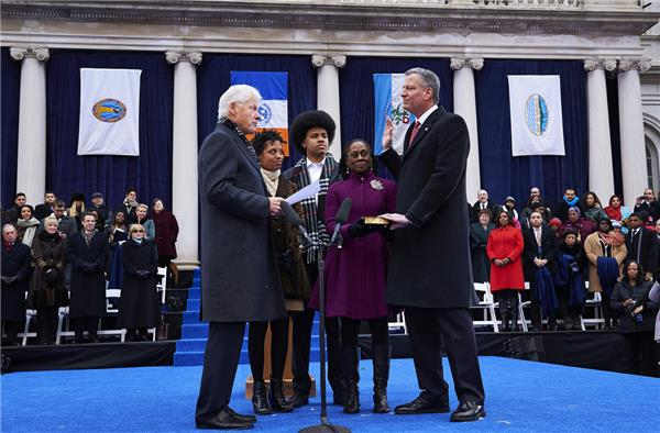 Former President Clinton swears in New York City Mayor de Blasio on Wednesday at City Hall as the first family looks on.