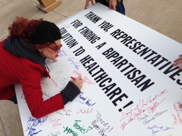 Tonya Estell of Conway signs a giant card thanking Arkansas State Legislature for passing Obamacare healthcare expansion.