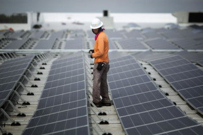 Neil Black works on the installation of South Florida's largest solar panel array atop the future IKEA store