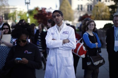 Doctor Vivek Murthy stands among other bystanders during the first day of legal arguments over the Affordable Care Act outside the Supreme Court in Washington March 26, 2012