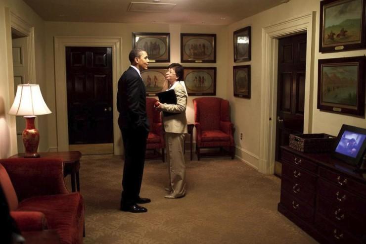 image of President Barack Obama and Senior Advisor Valerie Jarret chatting outside the Oval Office in the West Wing corridor of the White House.