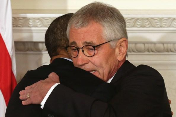 President Obama hugs Secretary of Defense Chuck Hagel during a press conference announcing Hagel's resignation in the State Dining Room of the White House