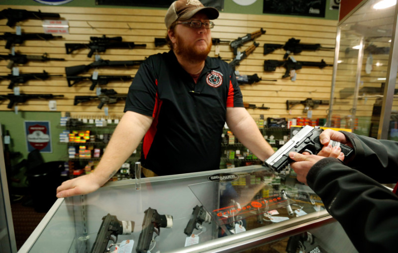 File - Metro Shooting Supplies' employee Chris Cox speaks to a customer about the purchase of a 9mm handgun in Bridgeton, Missouri, November 13, 2014. | Reuters/Jim Young
